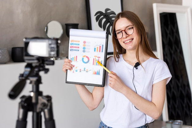 Young blogger recording with professional camera holding clipboard with graphics Free Photo