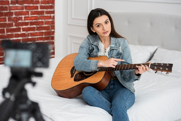 Young blogger teaching how to play guitar Free Photo