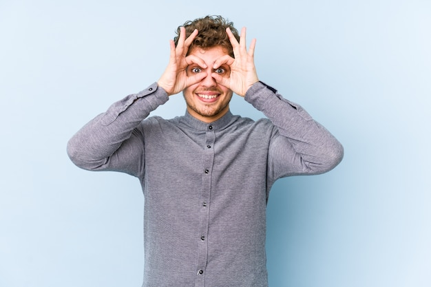 Young blond curly hair caucasian man isolated showing okay sign over eyes Premium Photo