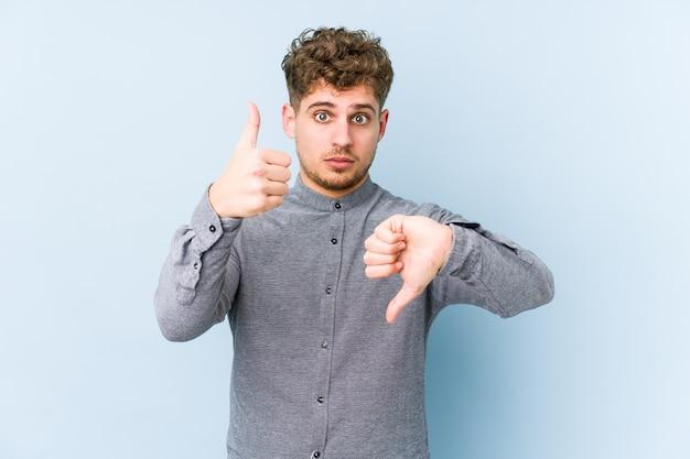 Молодой кавказский мужчина со светлыми вьющимися волосами изолирован, показывая большие пальцы руки вверх и вниз, трудно выбрать концепцию Premium Фотографии