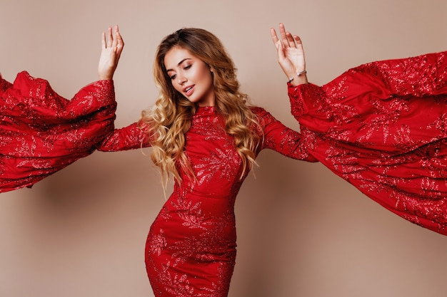 Young blond lovely woman in luxurious red dress with wide sleeves. expressive pose. Free Photo