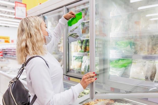 Молодая блондинка женщина в медицинской маске в отделе замороженных продуктов. здоровье и правильное питание во время пандемии. Premium Фотографии