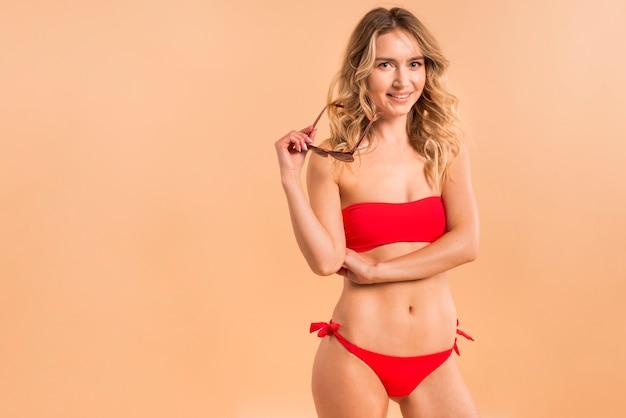 Young blond woman in red bikini on orange background Free Photo