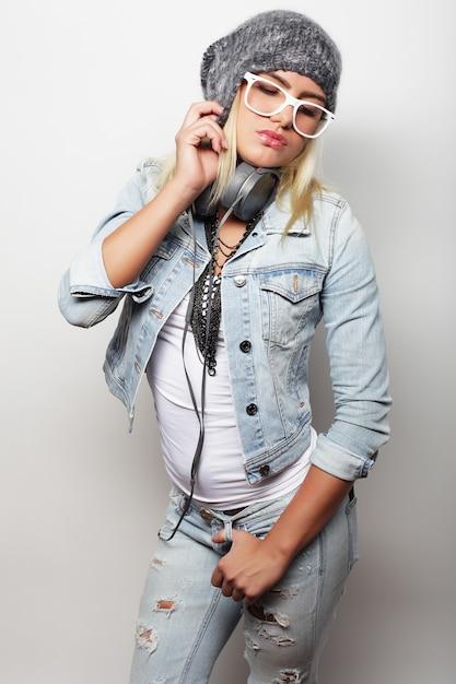 白い背景の上にカジュアルな服、流行に敏感なスタイルを身に着けている若いブロンドの女性 Premium写真