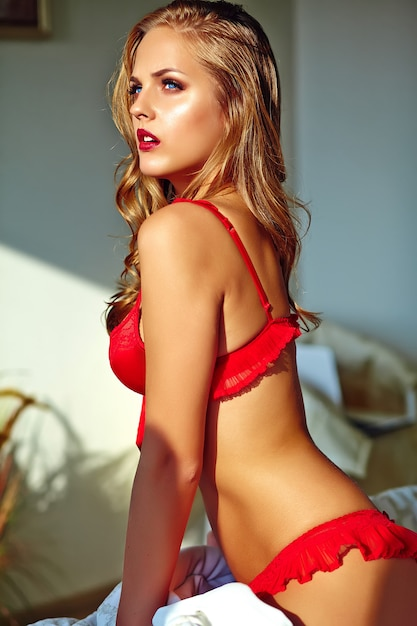 Young blond woman wearing red lingerie sitting on bed in the morning Free Photo