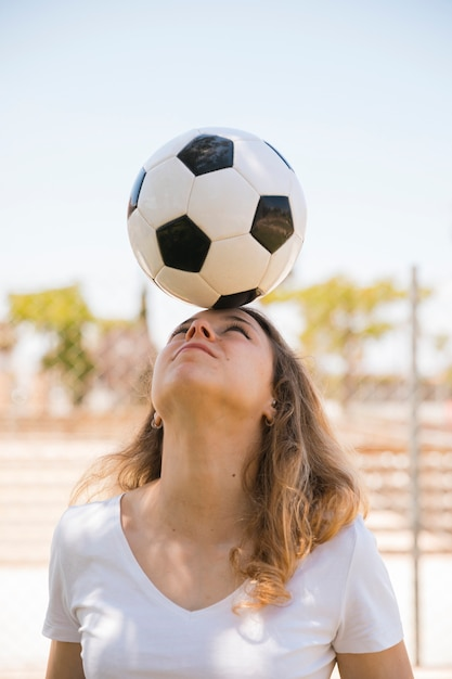 Young blonde balancing soccer ball on head in stadium Free Photo