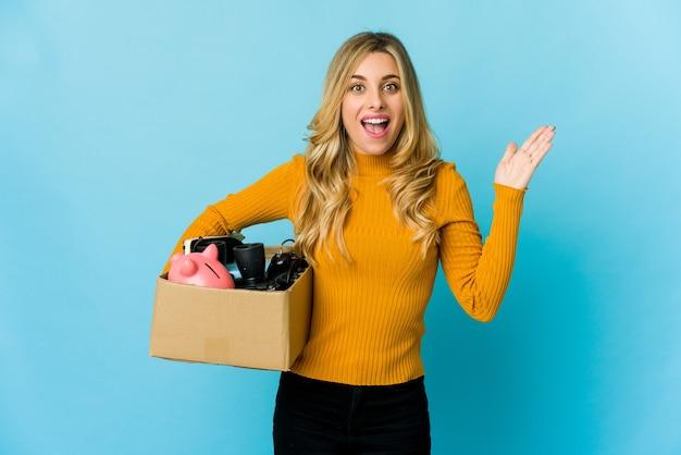 즐거운 놀라움을 받고 손을 올리는 이동 상자를 들고 젊은 금발의 백인 여자. 프리미엄 사진