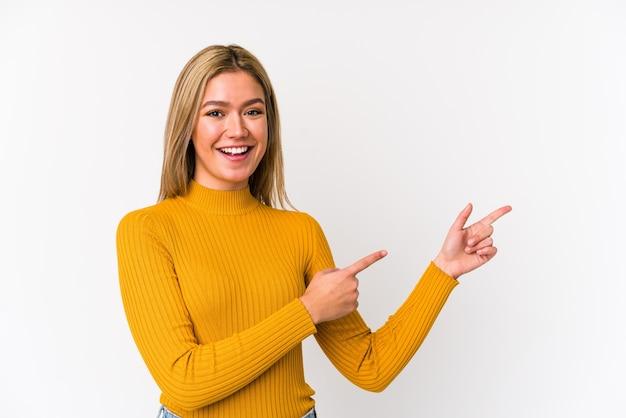 Молодая белокурая кавказская женщина изолировала возбужденное указывая указательными пальцами прочь. Premium Фотографии