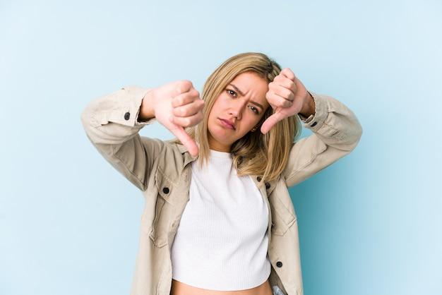 Молодая белокурая кавказская женщина изолировала показывая большой палец вниз и выражая неприязнь. Premium Фотографии