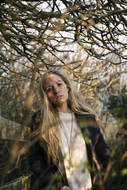 Giovane femmina bionda con un mantello nero in piedi su un sentiero circondato da alberi spogli Foto Gratuite