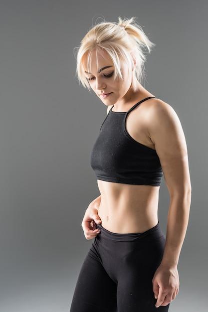 黒いスポーツウェアの若いブロンドフィットスポーティな女の子女性は彼女の強い筋肉ボディのストレッチを実証します 無料写真