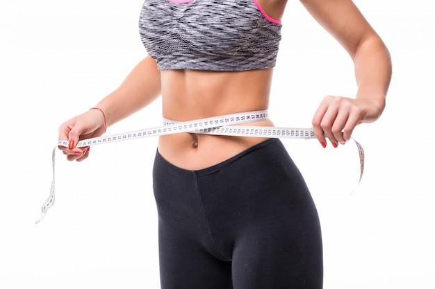 若い金髪フィットネス女性の重量の概念を失うファッションスポーツウェアに身を包んだ定規で彼女の体を測定 無料写真