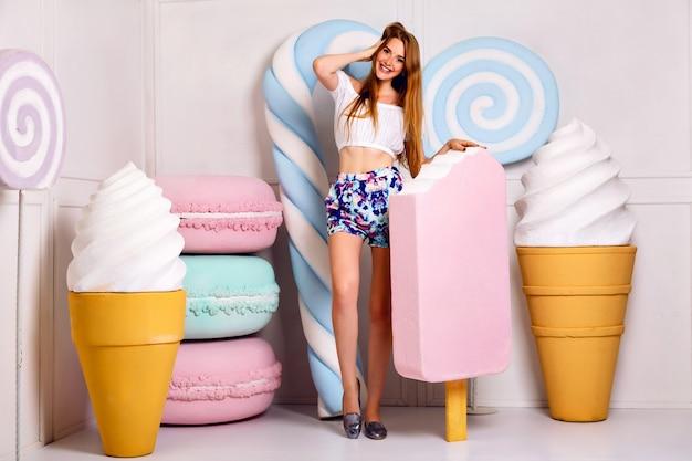 Молодая блондинка смешная женщина позирует в студии возле гигантской сладости, держа большое мороженое, миндальное печенье Бесплатные Фотографии
