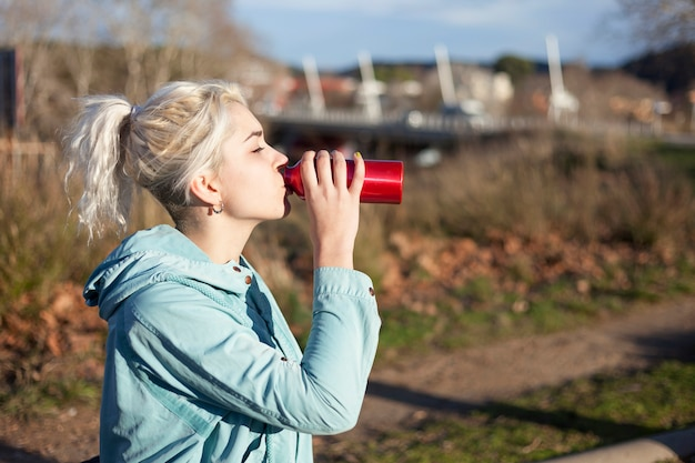 Young blonde girl drinking water during morning jogging Premium Photo