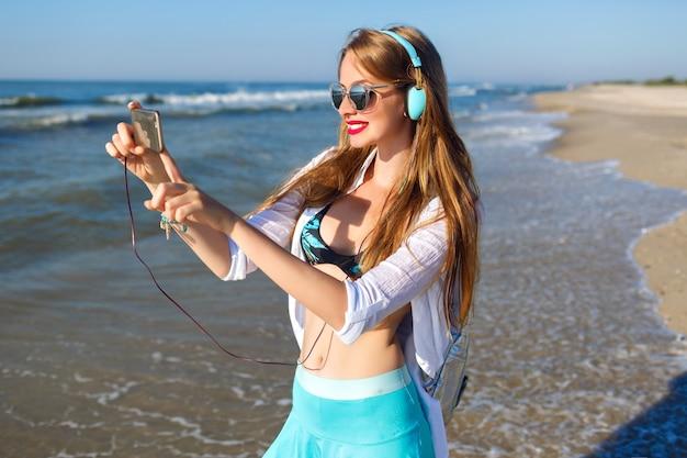 Молодая блондинка веселится на пляже, яркое закрытие битника, отдых у океана, слушает расслабляющую музыку и делает селфи на своем телефоне. Бесплатные Фотографии
