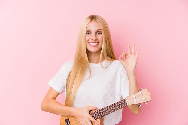 ウクレレを元気で自信を持ってokのしぐさを示す若いブロンドの女の子。 Premium写真