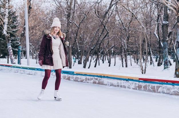 雪に覆われた冬の公園でスケートをしている若いブロンドの女の子。 Premium写真