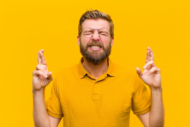 Young blonde man feeling nervous and hopeful, crossing fingers, praying and hoping for good luck against orange wall Premium Photo