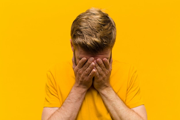 Young blonde man feeling sad, frustrated, nervous and depressed, covering face with both hands, crying against orange wall Premium Photo