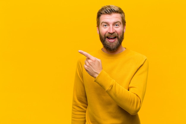 Young blonde man looking excited and surprised pointing to the side and upwards to copy space against orange wall Premium Photo