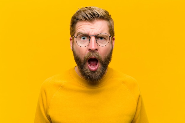 Young blonde man looking shocked, angry, annoyed or disappointed, open mouthed and furious against orange wall Premium Photo