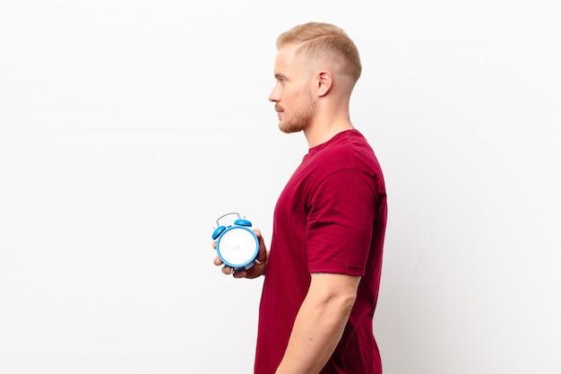 目覚まし時計を保持している白い壁に、先にスペースをコピーすることを考えて、考えて、想像して、または空想にふける縦断ビューで若い金髪の男 Premium写真