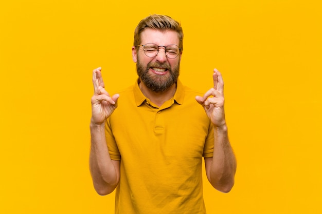 Young blonde man smiling and anxiously crossing both fingers, feeling worried and wishing or hoping for good luck Premium Photo