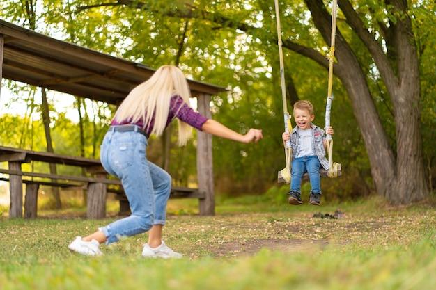 若いブロンドのお母さんは、緑豊かな公園のブランコで彼女の幼い息子を振る。幸せな子供時代。 Premium写真