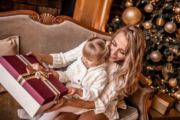 Young blonde mother and her daughters in white knitted clothes opening a magical christmas gift by a christmas tree in cozy living room in winter Premium Photo