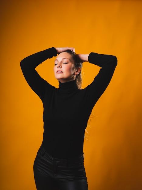 Молодая блондинка кладет руки на волосы, делая высокий хвост, закрывая глаза, в черной рубашке и брюках Premium Фотографии