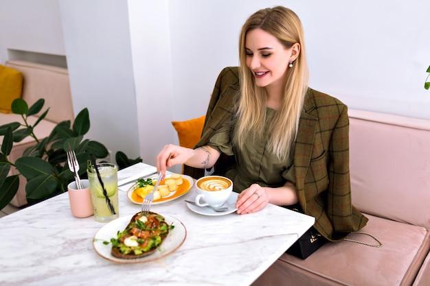 サーモンアボカドトースト、カプチーノ、レモネード、デザート、エレガントな衣装、派手なインテリアでおいしい健康的なブランチを楽しむ若い金髪のかなり笑顔の女性。 無料写真