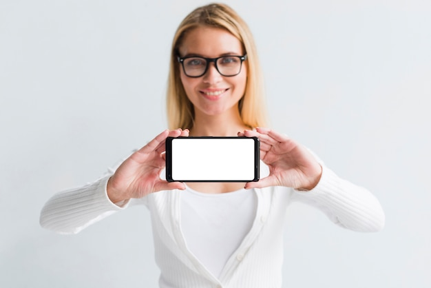 Young blonde showing smartphone screen Free Photo