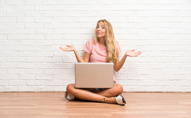 Young blonde student girl with a laptop on the floor having doubts with confuse face expression Premium Photo