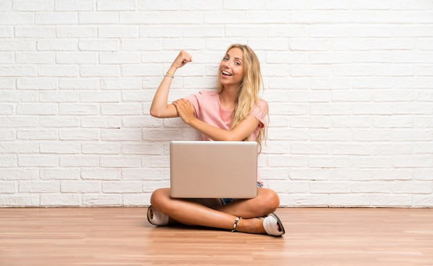 Young blonde student girl with a laptop on the floor making strong gesture Premium Photo