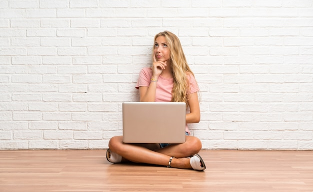 Young blonde student girl with a laptop on the floor thinking an idea Premium Photo