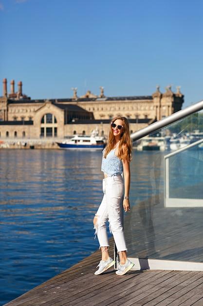 バルセロナの若いブロンドの旅行、スタイリッシュな服とサングラス、海と建築の素晴らしい景色。 無料写真