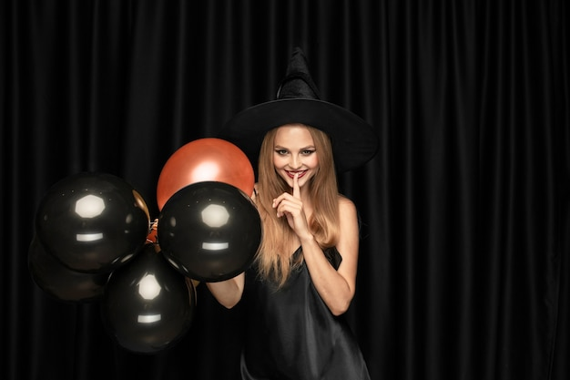 Young blonde woman in black hat and costume on black background. attractive, sensual female model. halloween, black friday, cyber monday, sales, autumn. copyspace Free Photo