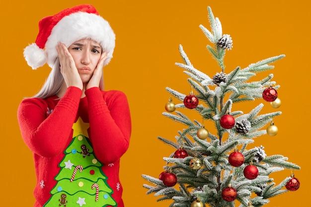 Giovane donna bionda in maglione di natale e santa hat guardando la telecamera confusa e molto ansiosa in piedi accanto a un albero di natale su sfondo arancione Foto Gratuite