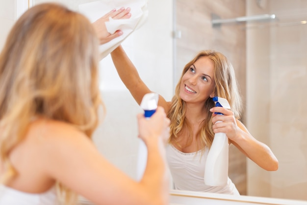 Young blonde woman cleaning mirror in bathroom Free Photo