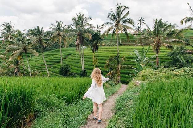 Young blonde woman dance on the rice fields of bali island, indonesia. Premium Photo