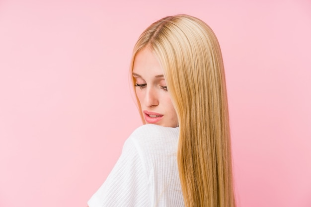 Young blonde woman face closeup isolated on a pink background Premium Photo