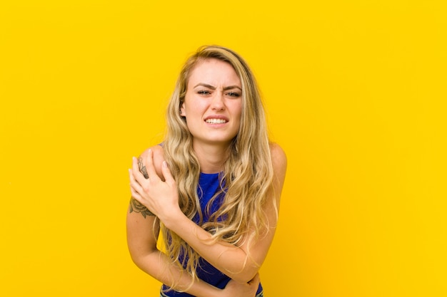 Young blonde woman feeling anxious, ill, sick and unhappy, suffering a painful stomach ache or flu over yellow wall Premium Photo