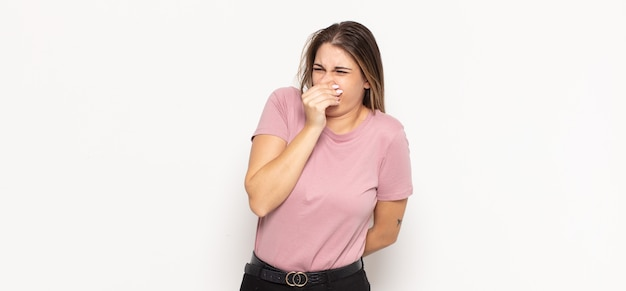 Young blonde woman feeling disgusted, holding nose to avoid smelling a foul and unpleasant stench Premium Photo