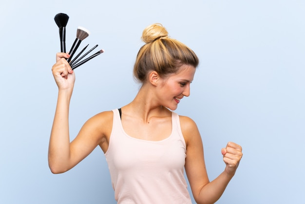 Young blonde woman holding lots of makeup brush celebrating a victory Premium Photo