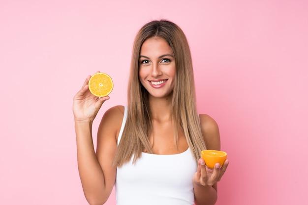 Young blonde woman holding an orange Premium Photo