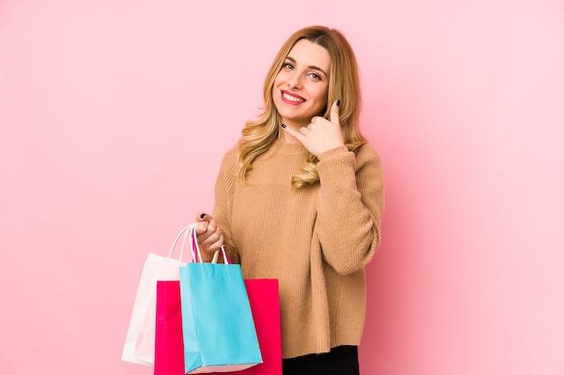 젊은 금발의여자가 손가락으로 휴대 전화 제스처를 보여주는 절연 쇼핑백을 들고. 프리미엄 사진