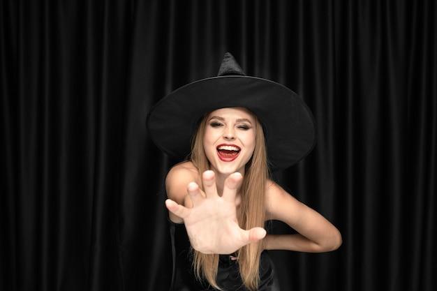 검은 모자와 검은 의상에서 젊은 금발 여자 무료 사진