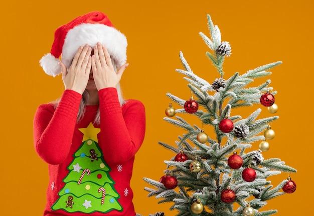 Молодая блондинка в рождественском свитере и шляпе санта-клауса c Бесплатные Фотографии