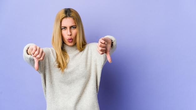 親指ダウンを示すと嫌悪感を表現する紫に分離された若いブロンドの女性。 Premium写真