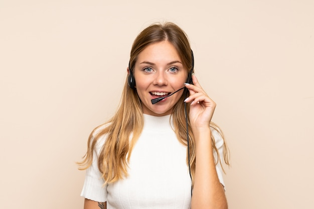 Young blonde woman over isolated wall working with headset Premium Photo